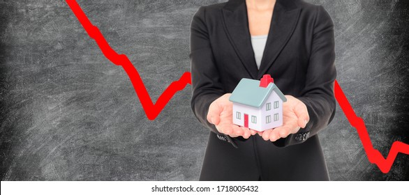 Real estate market crash due to recession economic downturn from coronavirus pandemic crisis. Realtor showing miniature home on red graph blackboard.