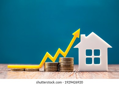 Real estate market, graph, up arrow. House model and a stack of coins. The concept of inflation, economic growth, the price of insurance services