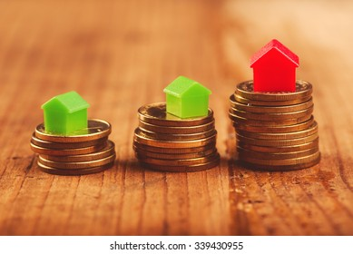 Real estate mortgage concept with small plastic house models on top of stacked coins.