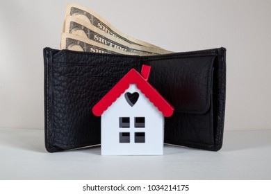 Real estate and mortgage investment. Being an easy way homeowner. The window is the heart of the house,wallet and dollars on the white background.
