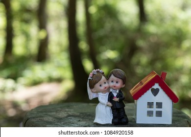real estate and mortgage investment. bride, groom and house on the wooden background.Being an easy way homeowner.