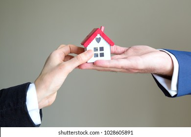 real estate and mortgage investment. the man holds house and dollars.