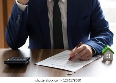 Real estate and mortgage investment. the man sign on the contract and hold pen.