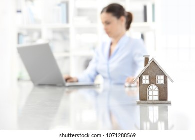 real estate office, home leaning on desk and woman agent working on computer in background
