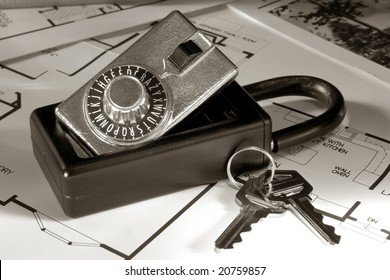 Real estate Realtor combination lock box with set of house keys over home builder construction layout floor plans