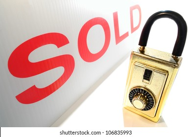 Real estate Realtor key holder combination lock box and professional house sale broker red sold sign insert over white