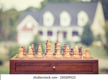 Real estate sale, home savings, loans market concept. Housing industry mortgage plan and residential tax saving strategy. Chess game figures isolated outside home background.