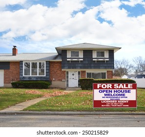 Real estate for sale open house welcome sign Suburban high ranch brick home autumn blue sky clouds day residential neighborhood USA