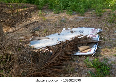 A Real estate for sale sign is laying on the ground under palm fronds after hurricane storm damage in florida.