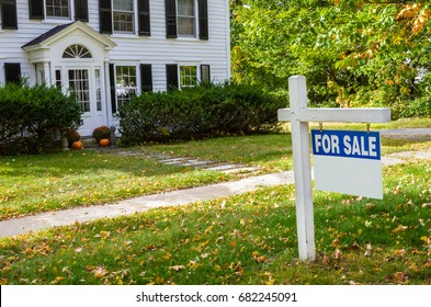 Real Estate Sign in Front of a Traditional Wooden House on Sale