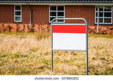 Real estate sign on a lawn in front of a red brick house with windows