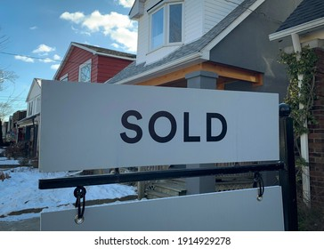 """A real estate """"sold"""" sign is seen in front of homes in the winter snow."""