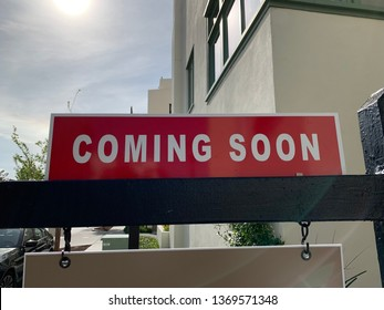 """A real estate sign that says """"Coming Soon""""."""