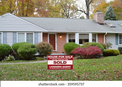 Real estate sold (another success let us help you buy sell your next home) sign Brick Ranch Home Autumn Fall Day residential neighborhood USA
