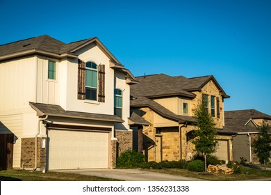 Real estate suburb development in Austin Texas evening afternoon sunset bright sunshine on front yards and facade of new homes in central Texas