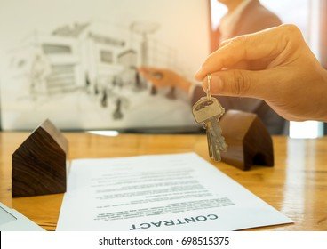 Real estate trading concepts,Close-up house key in hand the back is a house sketch,Model house and contract documents placed on the table.