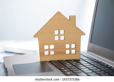 real estate, wooden house model on computer laptop