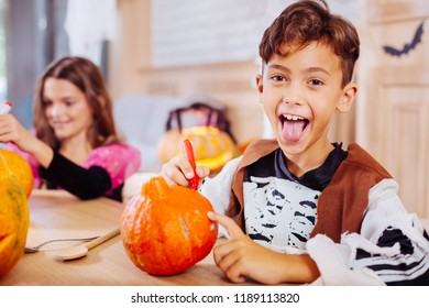 Real excitement. Cute beaming boy wearing Halloween costume showing his tongue while feeling excited