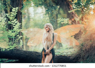 real fairy from magical stories, goddess of nature with transparent wings alone in dense forest, beauty closes her eyes, listens to birds singing, charming lady in the sunlight and with bare legs.