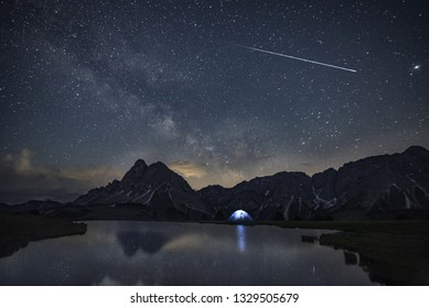 Real falling star with darkness sky are reflected in an alpine lake. The Milky Way and stars above a camping tent lit up in the night with the beautiful Dolomiti before the sunrise. Neowise Comet.