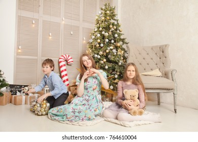 A real family, mother, daughter and son, are happy and have a nice time near the Christmas tree and gifts at home in the room