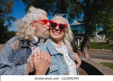 Real feelings. Delighted bearded man kissing his wife while showing his feelings to her