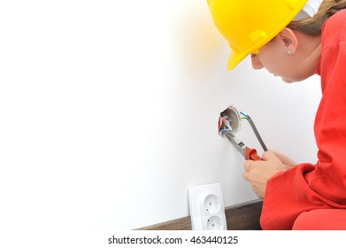 Real female electrician fixing socket electricity problem