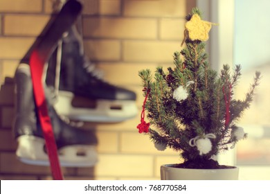 real festive Christmas tree decorated with knitted stars in pot against the window and wall on which hanging skates / good weather for winter holidays