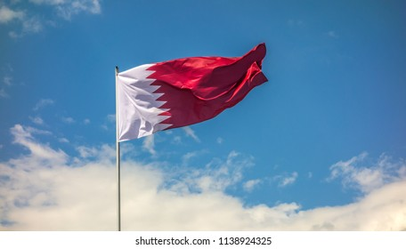 Real flag of the country Qatar waving in the wind against the background of a blue sky and clouds.