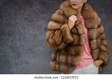 A real fur. Fur coat for winter. Brown. Grey background