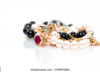 Real gold jewlery, diamonds, gems, rings, neckless with pearls close up shot , white background, on shiny surface.