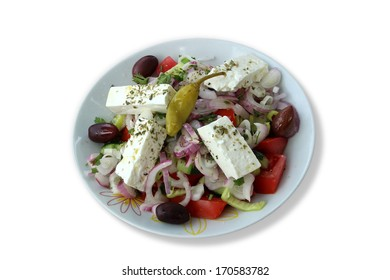 Real greek salad in a white plate isolated on white background