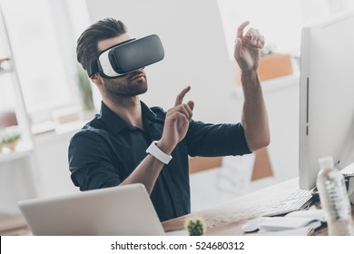 It is so real! Handsome young man in VR headset gesturing and smiling while sitting in creative office