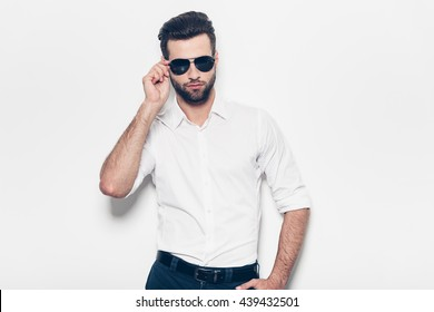 Real heartbreaker. Handsome young man in white shirt adjusting his sunglasses and looking at camera while standing against white background