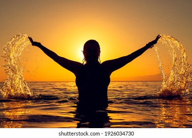 Real human body and female positivity concept: Confident and happy woman silhouette is playing in the sea at sunset. Retro style. Water splashing from her open hands and sun reflecting in the drops