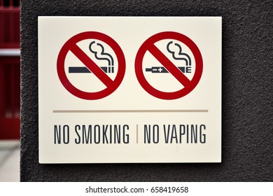 A real image of a no smoking and no vaping sign with symbols and text on the exterior of a residential building