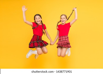 Real joy. happy little girls in checkered skirt. beauty look. happy children on yellow background. childhood happiness. trendy school uniform. funny jump. red fashion girls. english style fashion.