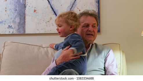 Real life candid natural family interaction. Grand-father holding little infant toddler baby grand-son in a casual cute candid natural family moment together seated on sofa