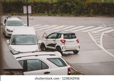 Real life photo of a inexperienced driver with a small moped style car or quadricycle caught in a crash with other cars. Danger of young and unexperienced drivers