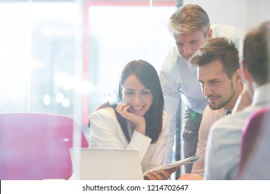 Real life small business meeting with four attractive business people have a discussion and looking at a laptop whilst drinking coffee. This is a typical workplace of a small business