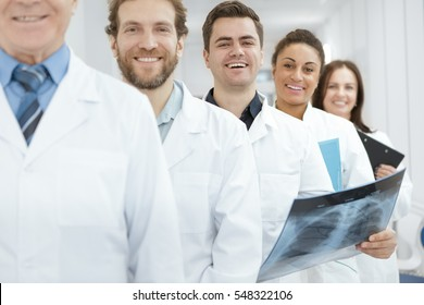 Real life superheroes. Cheerful young male doctor smiling to the camera holding an x-ray scan standing in a row with his colleagues at the hospital healthcare doctors professionals wellbeing concept