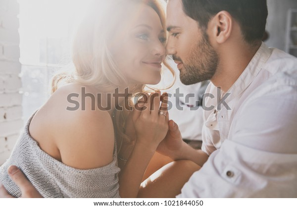本当の愛。寝室に座りながら、絆を結び、微笑む美しい若い夫婦