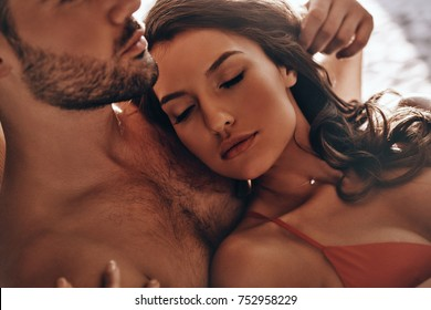 Real love.  Beautiful young woman sleeping in her boyfriends arms while resting on the beach together