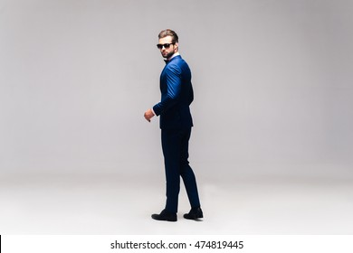 Real macho. Full length studio shot of handsome young man in full suit and bow tie looking over shoulder