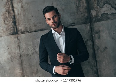 Real macho. Handsome young man in suit looking at camera and smiling while standing indoors