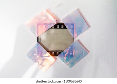 real macro photo of empty and blank 35mm filmstrip on white paper background with holo stickers on border edges, blend in your photo here, cool photo placeholder, shiny cellotape on film