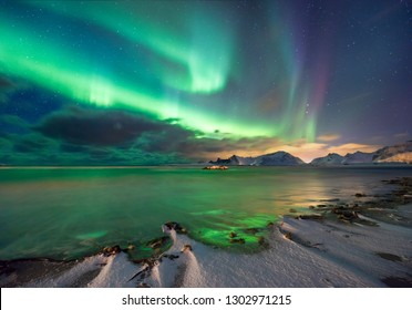 Real Magic of Northern Lights - Norwegian fjord with snow and mountains, color reflections on sea waves. Winter Landscape, northern nature