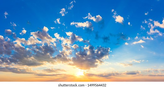 Real majestic sunrise sundown sky with sun, sun rays and colorful clouds, huge size