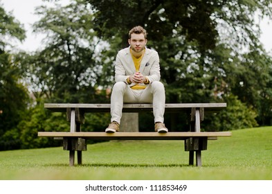 Real man well dressed staying on a bench having a white suit
