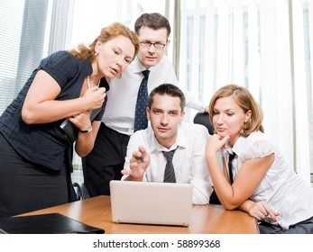 Real manager man communicating with his office workers during meeting in board room. Man explaining business strategy and showing it on the laptop computer.